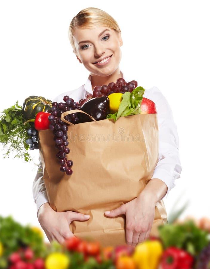 Ung kvinna med en livsmedelsbutikshoppingpåse. arkivbild