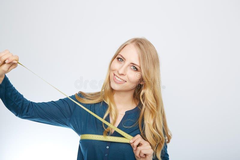 Ung kvinna med en måttband arkivfoto