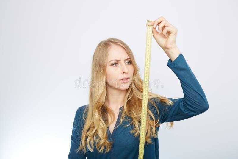Ung kvinna med en måttband royaltyfri bild