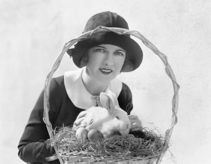 Ung kvinna med en påskkorg och en kanin (alla visade personer inte är längre uppehälle, och inget gods finns Leverantörwarranti royaltyfria foton