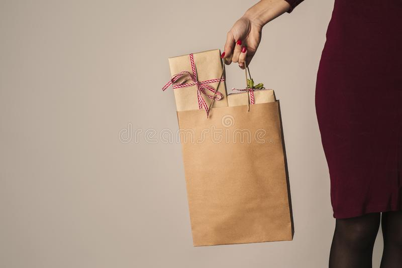 Ung kvinna med en pappers- shoppa påse mycket av gåvor royaltyfri foto