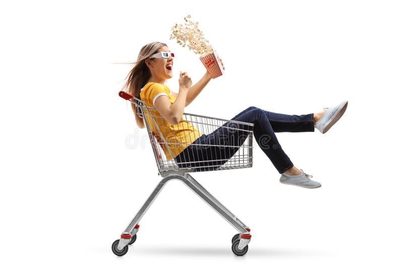 Ung kvinna med en popcornask och exponeringsglas som 3D rider inom ett sh arkivbilder