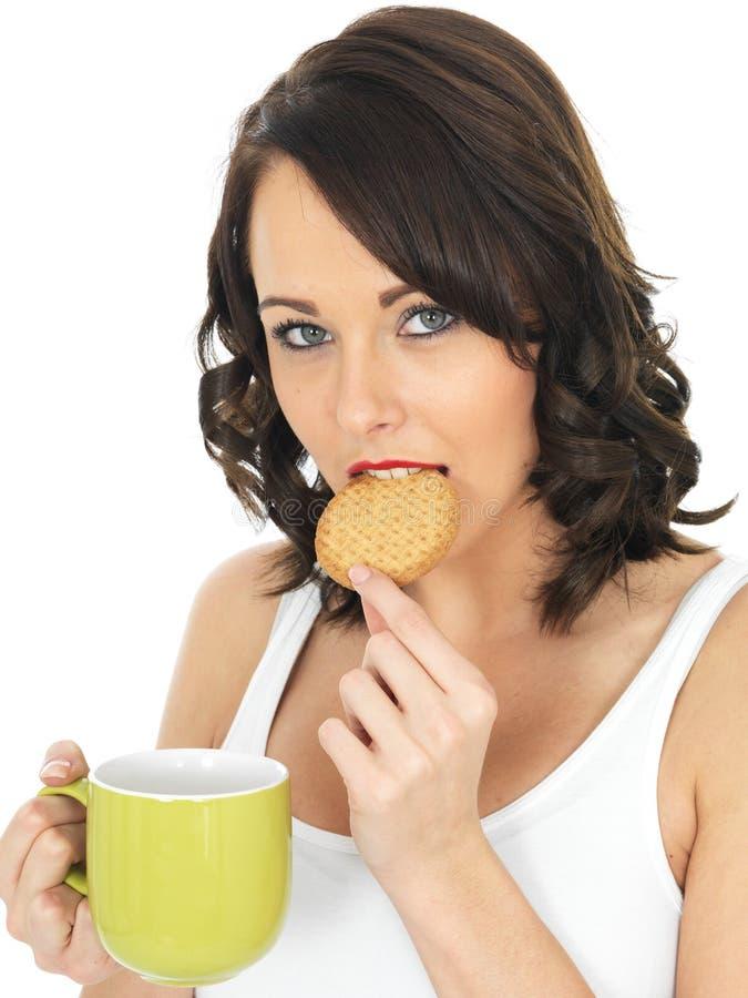 Ung kvinna med en råna av te och kexet arkivfoton