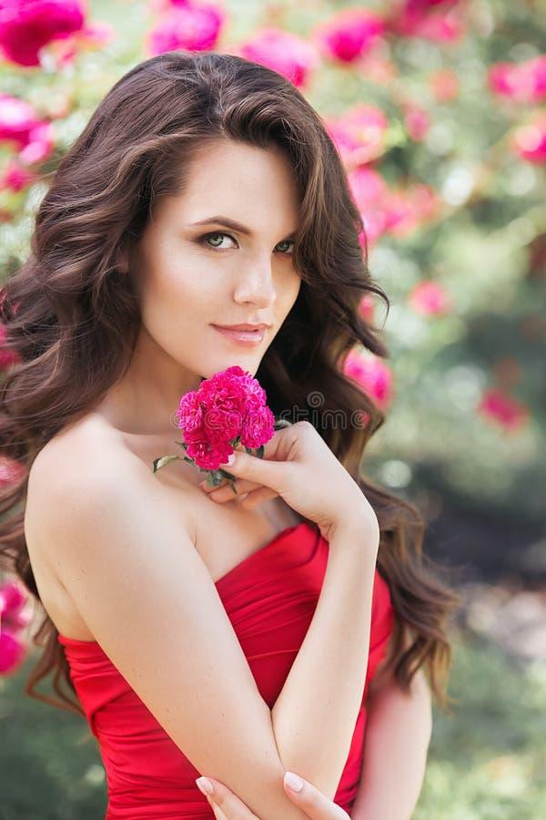 Ung kvinna med en rosa blomma Utomhus- sommarskott arkivbilder