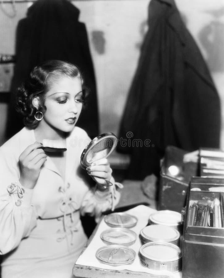 Ung kvinna med en sminkborste som ser hennes framsida i en handspegel (alla visade personer inte är längre uppehälle och inget go royaltyfri fotografi