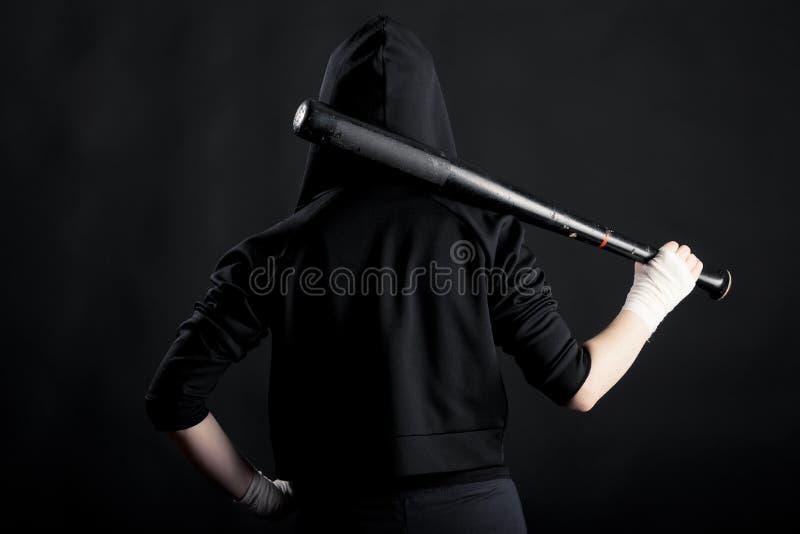 Ung kvinna med ett baseballslagträ tillbaka sikt hoodlum arkivfoton