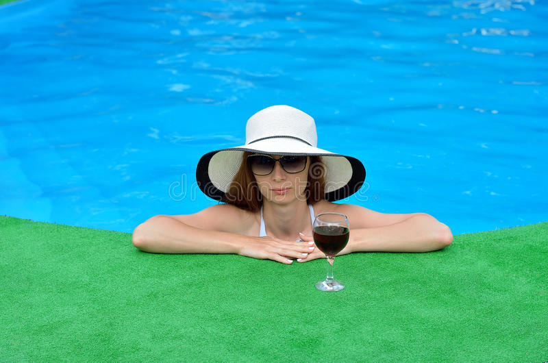 Ung kvinna med ett exponeringsglas av rött vin på kanten av pölen royaltyfri fotografi