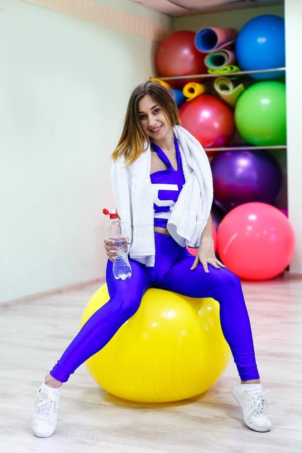 Ung kvinna med ett handduksammanträde på en boll som rymmer en flaska av w arkivbild
