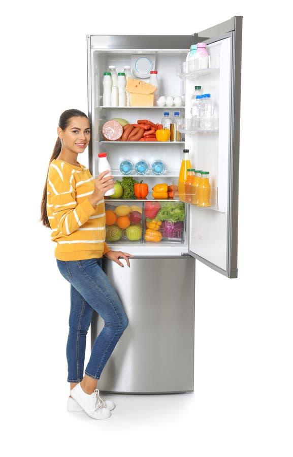 Ung kvinna med flaskan av för yoghurt det öppna kylskåpet nära royaltyfri bild