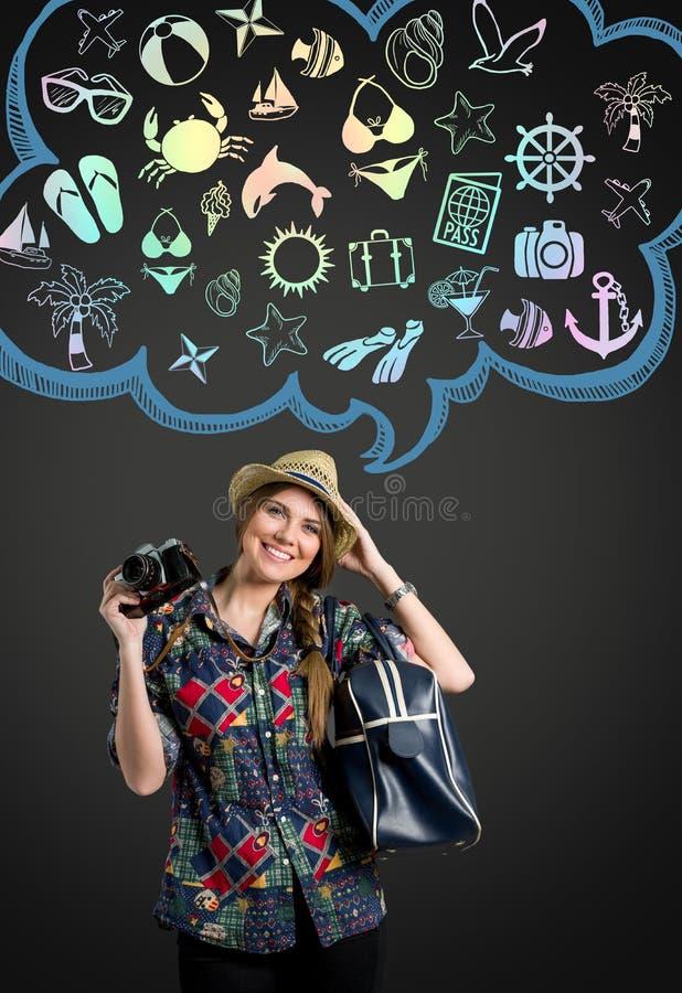 Ung kvinna med fotokameran som tänker på semester royaltyfria foton
