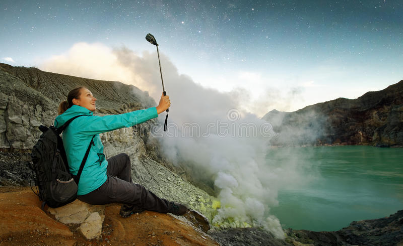 Ung kvinna med fotvandraren som överst tar vulkan för selfie royaltyfri fotografi