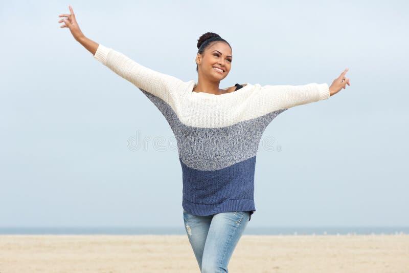 Ung kvinna med gladlynt uttryck och utsträckta armar royaltyfri foto