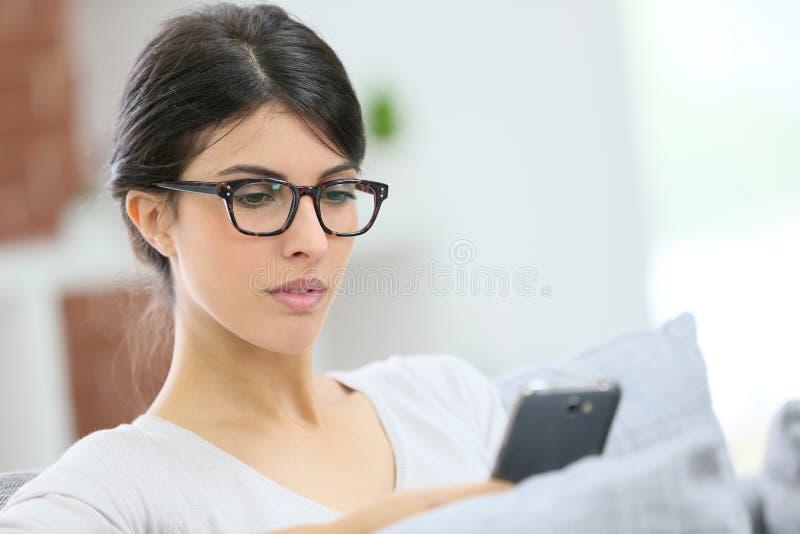 Ung kvinna med glasögon på smartphonen royaltyfri fotografi