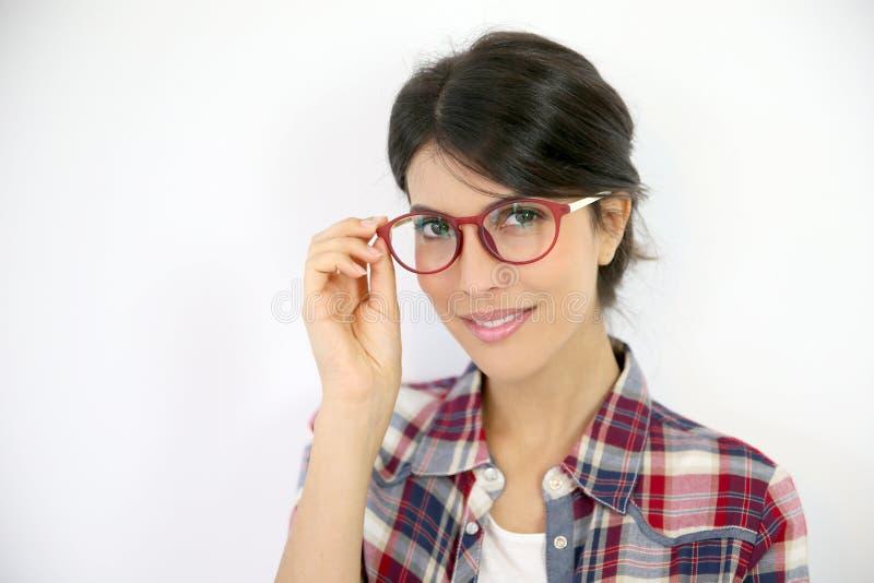 Ung kvinna med glasögon på vit bakgrund royaltyfri bild