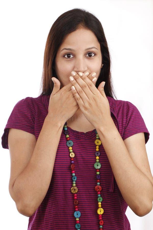 Ung kvinna med händer över mun royaltyfri foto