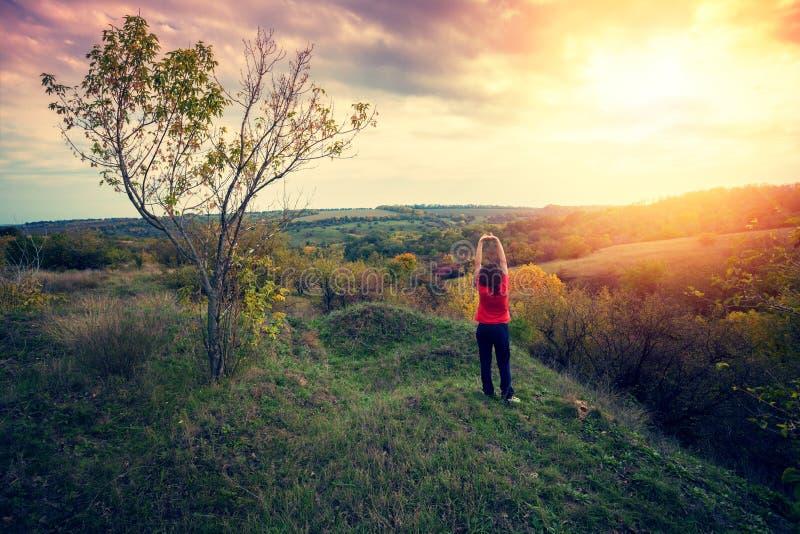 Ung kvinna med händer upp ställningar på överkanten av en kulle arkivbild