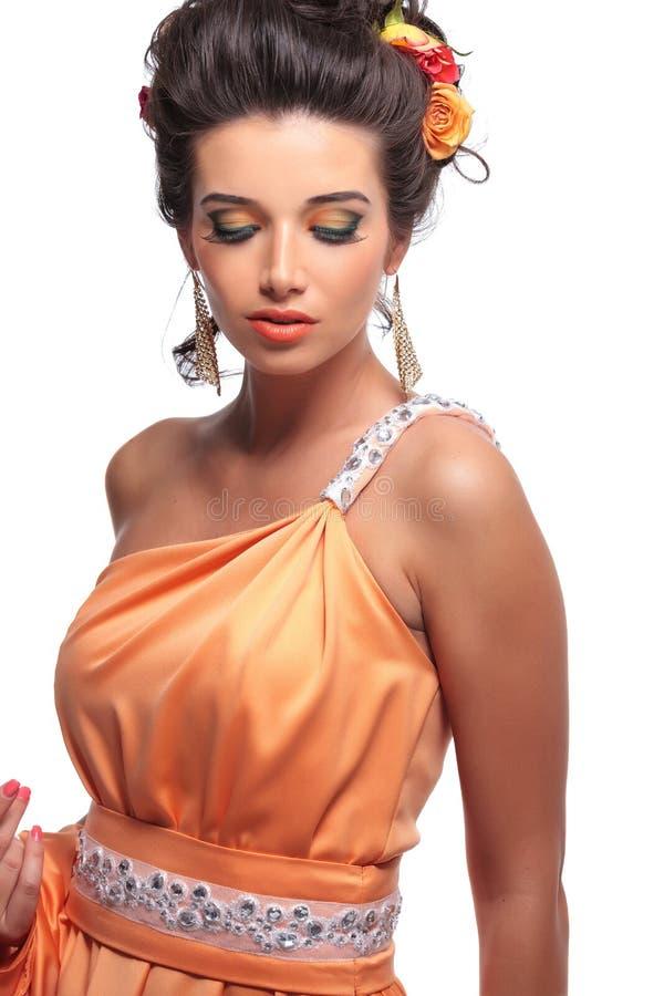 Ung kvinna med härlig makeup och blommor i hennes hårlookin fotografering för bildbyråer