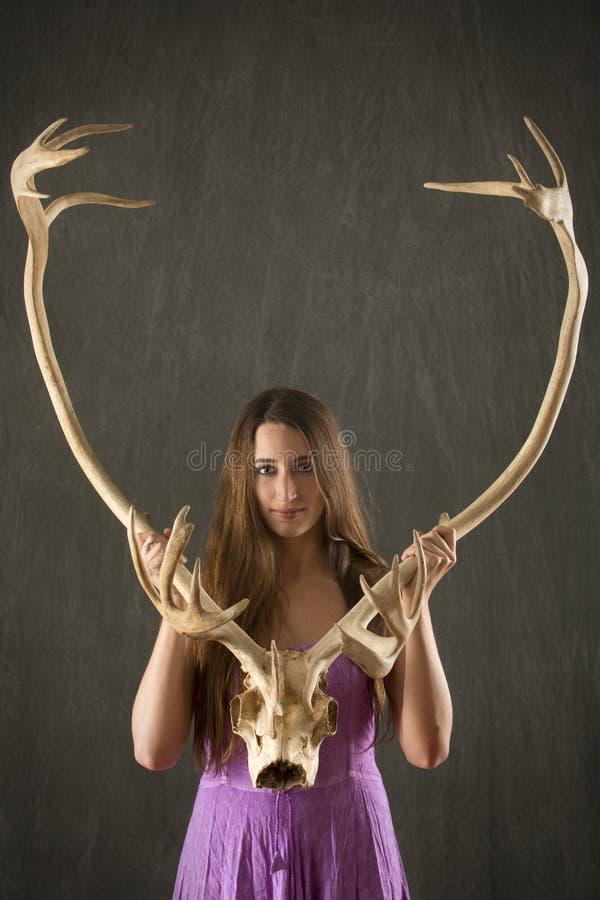 Ung kvinna med hållande karibuhorn på kronhjort för långt brunt hår fotografering för bildbyråer