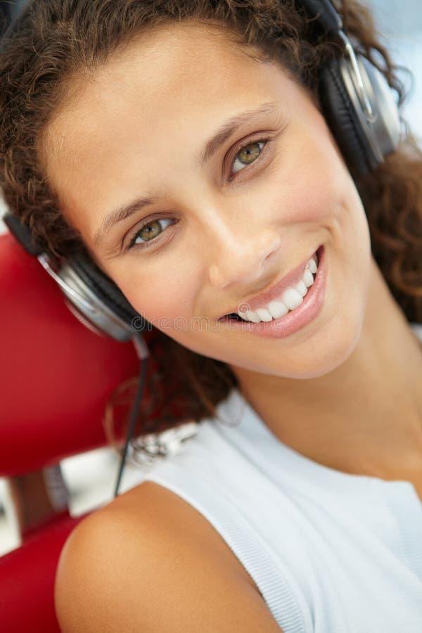 Ung kvinna med hörlurar royaltyfri foto