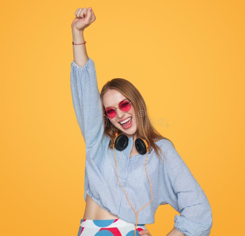 Ung kvinna med hörlurar som firar seger arkivfoto