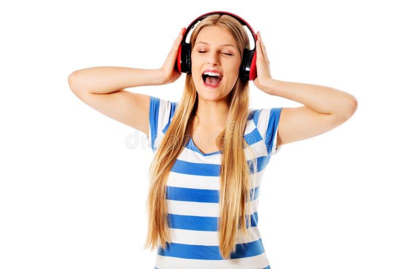 Ung kvinna med hörlurar som lyssnar och sjunger till musik som isoleras på vit royaltyfri bild