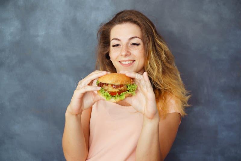 Ung kvinna med hamburgaren i händer som tycker om mat arkivfoton