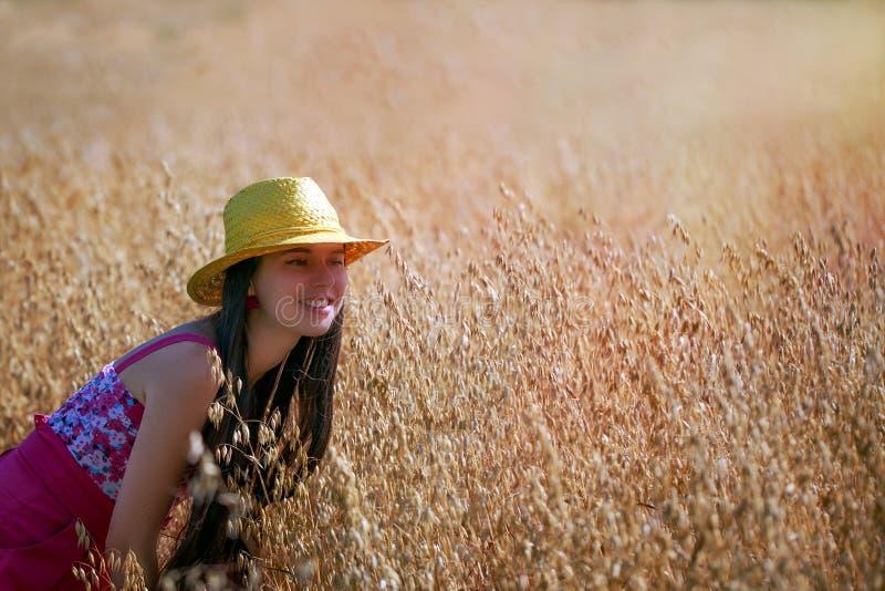 Ung kvinna med hattanseende på havrefältet arkivbilder