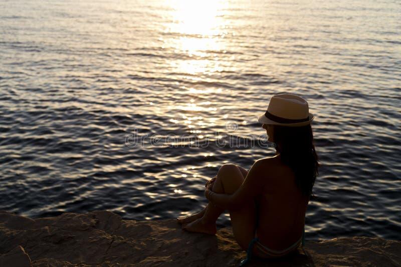 Ung kvinna med hatten på solnedgången royaltyfri foto