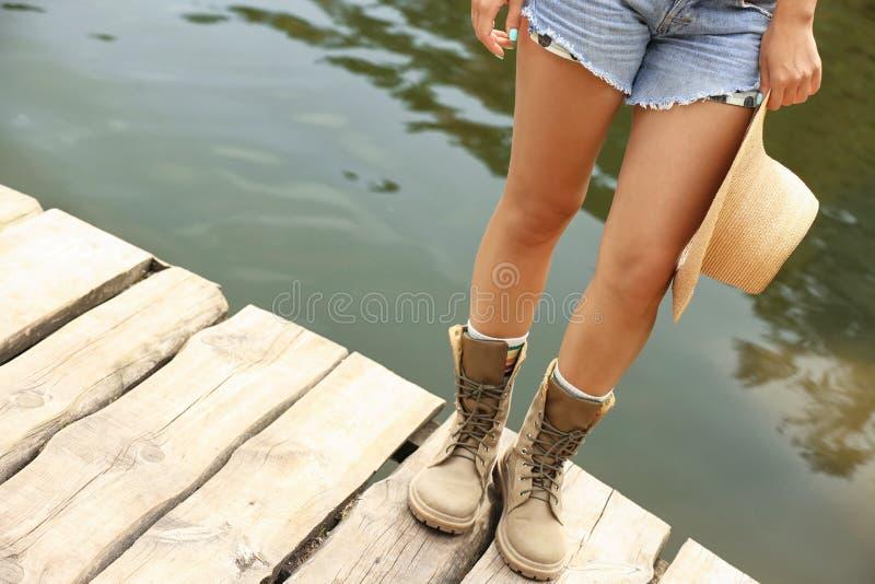 Ung kvinna med hatten på träpir nära sjön, fotografering för bildbyråer