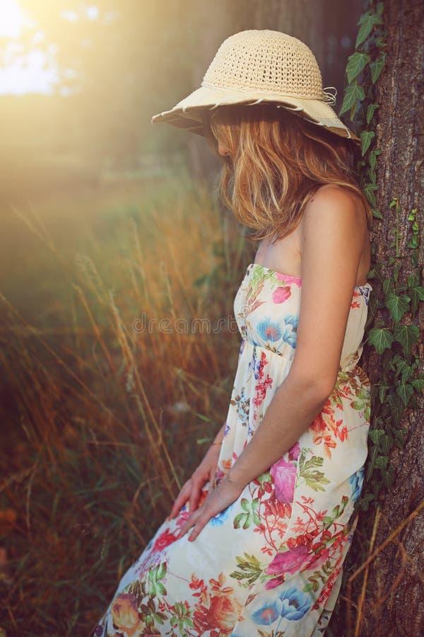 Ung kvinna med hatten som lutar till ett träd arkivbild