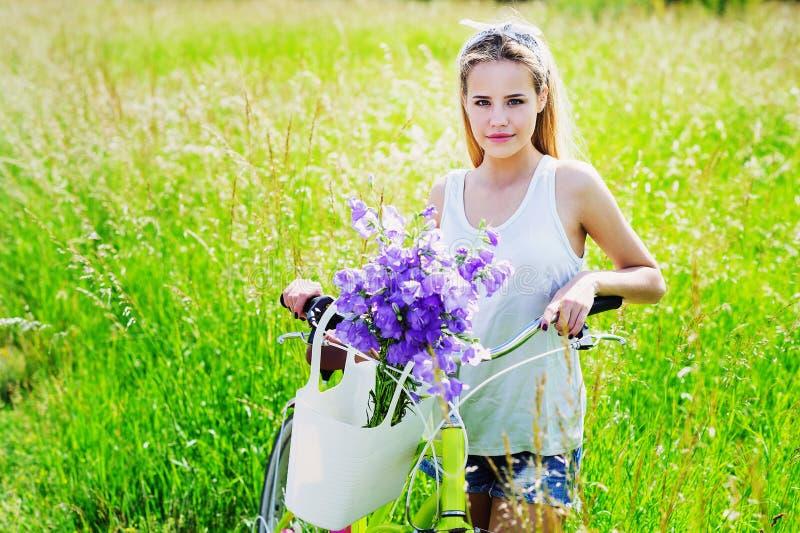 Ung kvinna med hennes cykel utomhus royaltyfria bilder