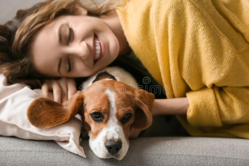 Ung kvinna med hennes hund som vilar på soffan royaltyfri foto