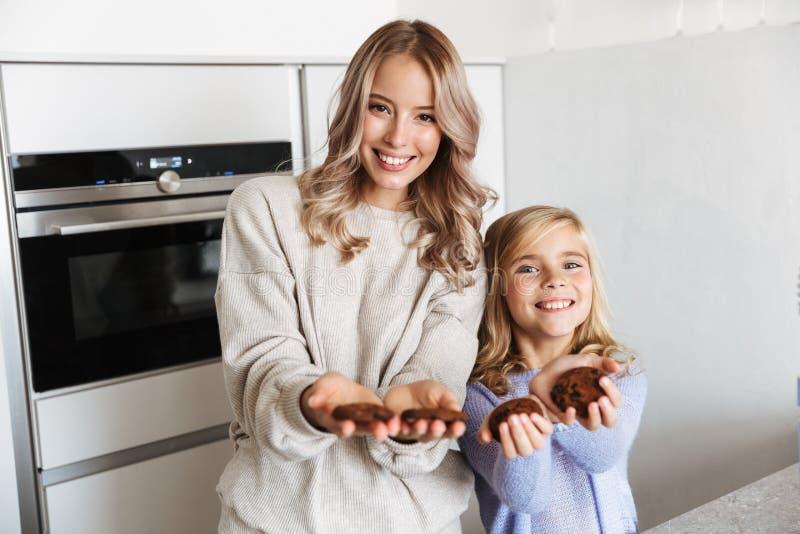 Ung kvinna med hennes lilla för syster som hemmastadda kök inomhus rymmer kakor royaltyfri foto