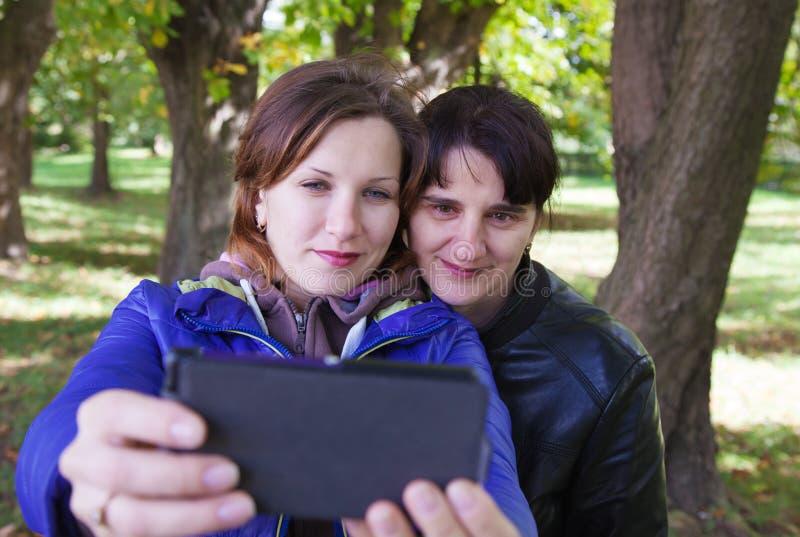 Ung kvinna med hennes moder som tar bilder av dem arkivfoton