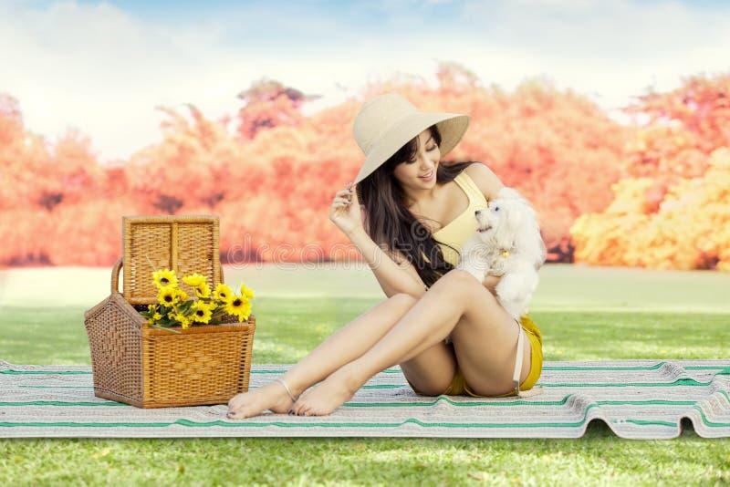 Ung kvinna med hundsammanträde på parkera royaltyfri bild