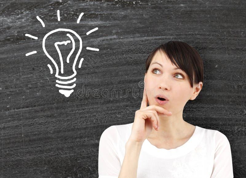 Ung kvinna med idéer som symbol av kreativitet royaltyfri foto