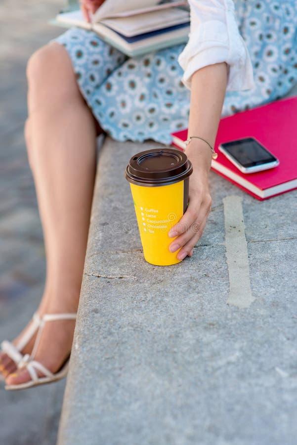 Ung kvinna med kaffe som går i staden arkivbild