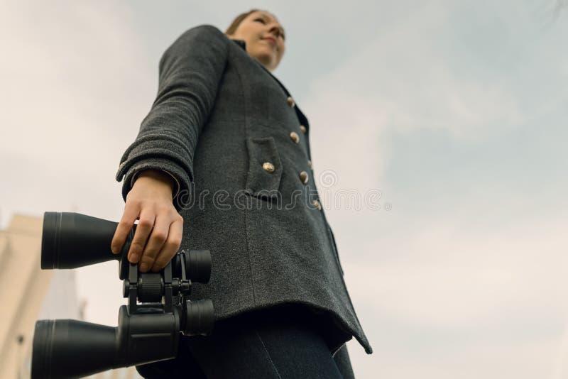 Ung kvinna med kikare som framåtriktat ser Utsikter för futur arkivfoto