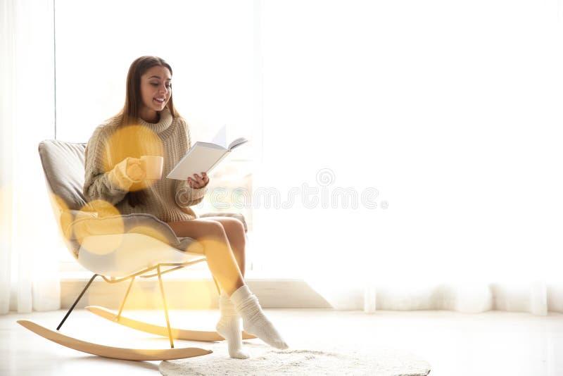 Ung kvinna med kopp kaffeläseboken nära fönster hemma royaltyfria bilder
