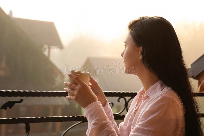 Ung kvinna med kopp te som tycker om härlig sikt royaltyfria bilder