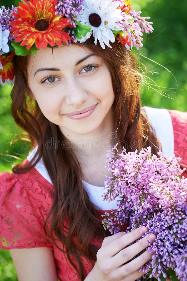 Ung kvinna med kransen och med lila blommor i vår royaltyfri foto