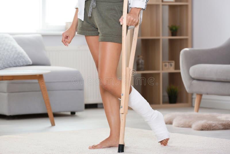 Ung kvinna med kryckan och benbrottet i ensemble hemma arkivfoton