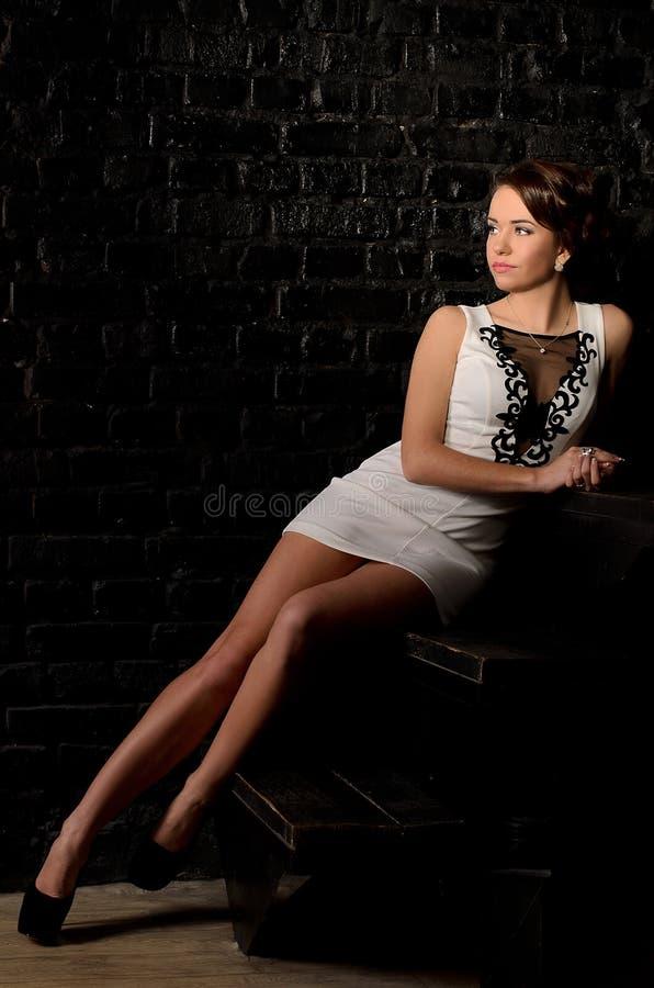 Ung kvinna med långa ben som sitter på trappa royaltyfri foto