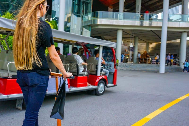 Ung kvinna med långa hår på den elektriska sparkcykeln Flickan på den elektriska sparkcykeln dricker kaffe royaltyfri foto