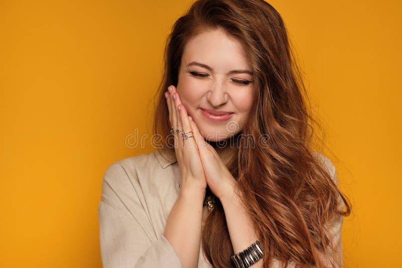 Ung kvinna med långa hårvindögdheter från lycka och njutning, gul bakgrund arkivbilder
