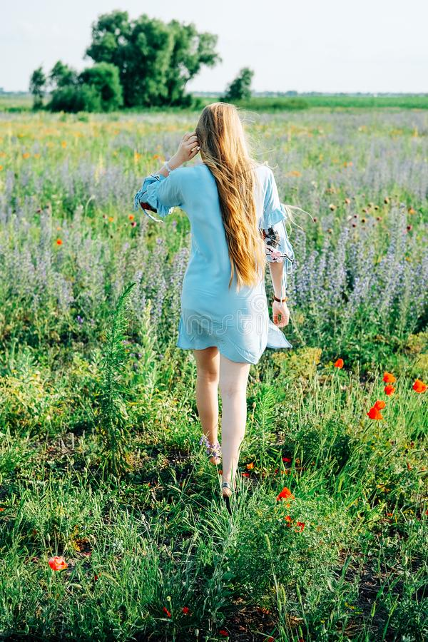 Ung kvinna med långt blont hår som bort går i fältet fotografering för bildbyråer