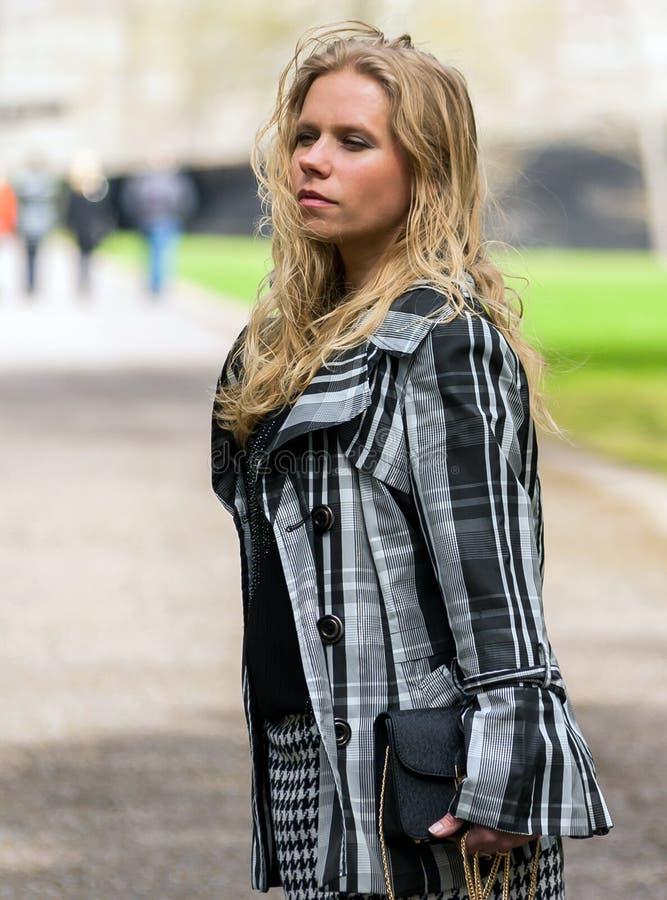 Ung kvinna med långt blont krabbt hår och ett randigt omslag royaltyfri fotografi