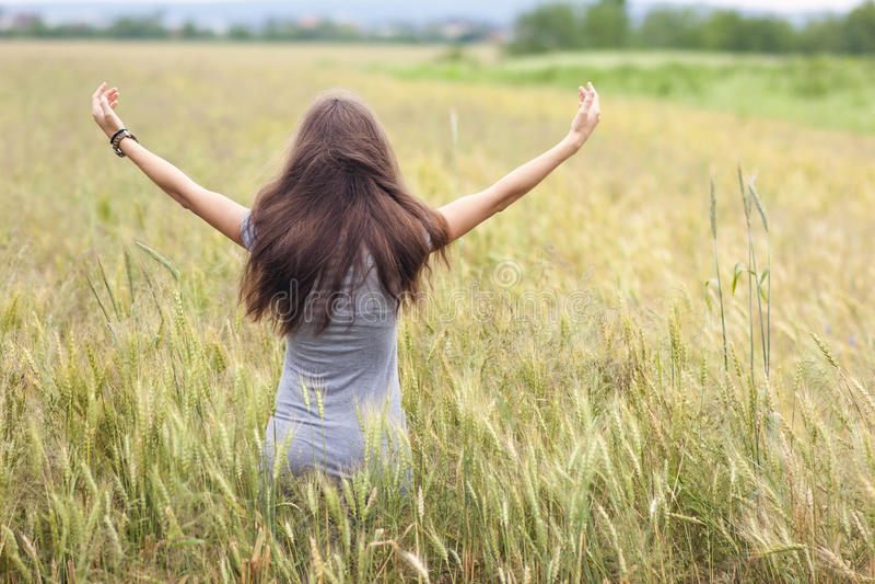 Ung kvinna med långt brunt håranseende, i att lyfta för vetefält arkivfoto