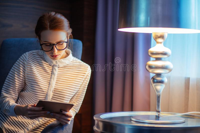 Ung kvinna med långt hår genom att använda minnestavlan och le sammanträde på soffan royaltyfri bild