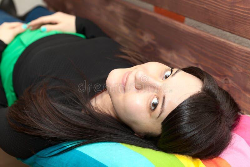 Ung kvinna med långt hår som tillbaka lägger, och blickar på kameran arkivbilder